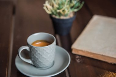 Cup coffee on White wooden table and old book and pot