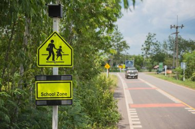 Yellow sign school zone symbol in the countryside