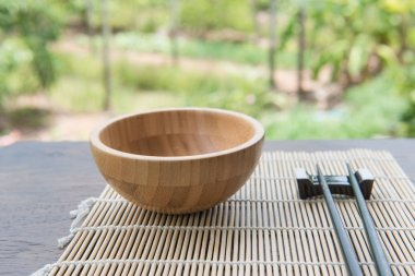 Wooden bowl with chopsticks on bamboo mat  on wooden table in the garden
