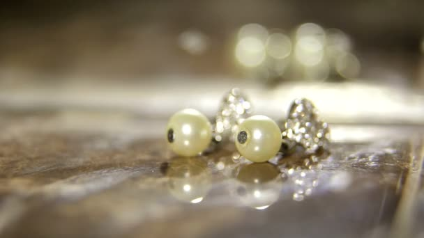 Earrings with pearls are on the table, illuminated by artificial light.