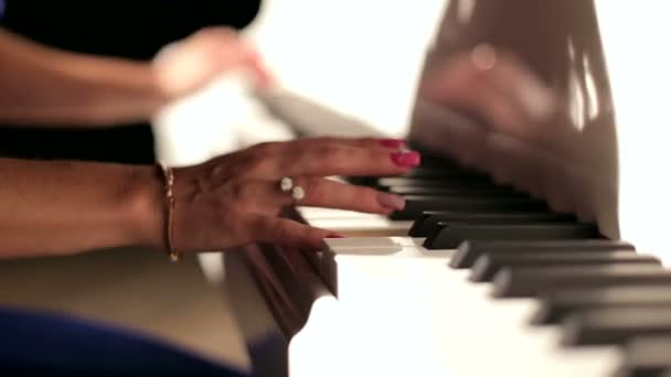 The hands of a woman as she is playing the piano. ?loseup.