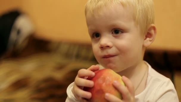 Cute little boy eating an Apple and waving his hand. Closeup.