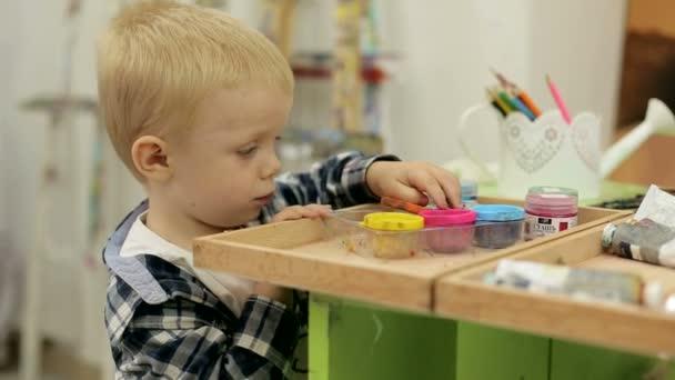 Chlapeček si hraje s barvou. Paleta barev. Dítě v ateliéru pro malování.