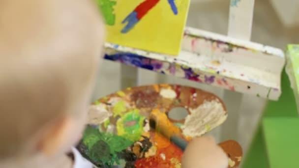 A kisfiú a gazdaság a palettán. Gyerek rajz festékek