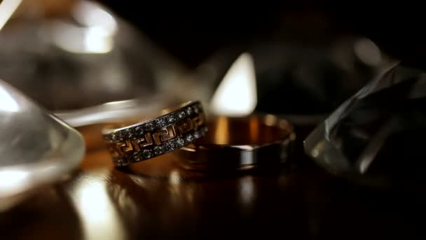 Two rings on a black iridescent background. Wedding rings. Golden rings close-up.