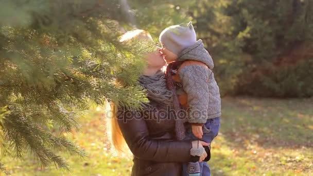 Matka drží dítě v náručí. Dítě líbání matka na jaře Park. Malé dítě obejme její matka