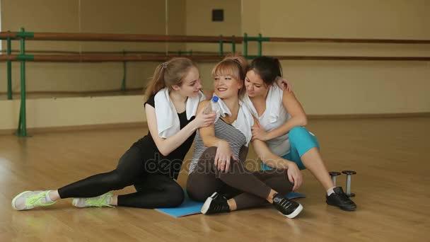 Tři krásné sexy dívky sedí ve školící místnosti a odpočinku po cvičení. Sport. Fitness