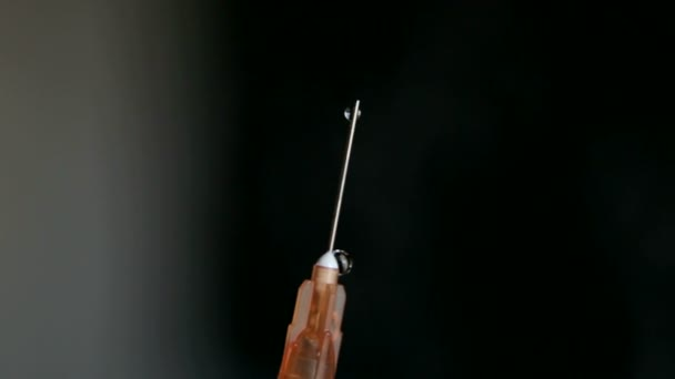 medizinische Spritze mit Nadel in Nahaufnahme auf schwarzem Hintergrund. die Nadel der Spritze und Tropfen Medikament.
