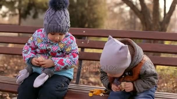Dvě malé děti čistit mandarinky. Bratr a sestra jíst mandarinky. Roztomilé děti sedět na lavičce a jíst