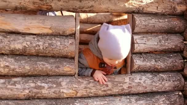 Milý chlapeček směje a při pohledu na fotoaparát. Šťastné dětství. Děti si hrají venku na podzim. Dětský dřevěný dům