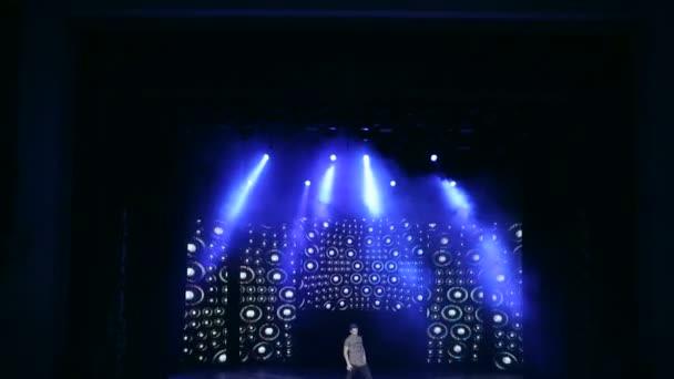Mladé tanečnice tančí hip-hop na jevišti s jasným světlem. Koncertní pódium. Osvětlení jeviště.