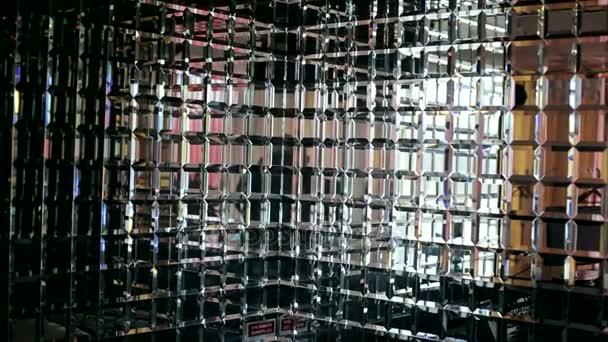 Krásnou zrcadlovou stěnou v jídelně. Zrcadlené svazky na pozadí. Stěna z malých, zrcadlové čtverečky. Zpomalený pohyb