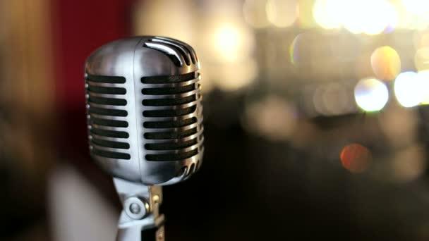 Vintage mikrofon egy karaoke bárban. A mikrofon erős fényben világító. Bokeh. Lassú mozgás.