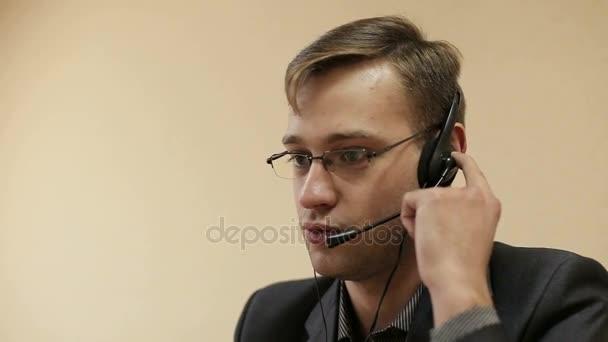 Detail z mužského call centra mluví do mikrofonu.