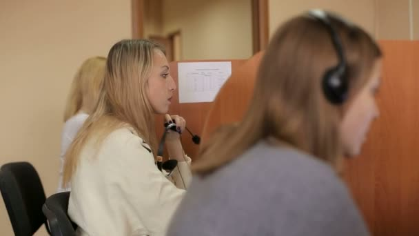Group of three customer care representatives in a call center with headphones.