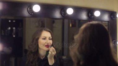 Sexy dívka namaluje rty s červenou rtěnkou na zrcadle. Kosmetický salon. Krása ženy