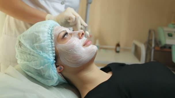 Žena s obličejové masky v salonu krásy. Kosmetické ošetření v salonu spa. Mladá žena pomocí kosmetické procedury. Kosmetička, použití masky na obličej zákazníka v salonu