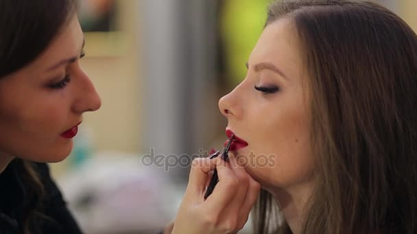 Make-up artist doing make-up to a client in a salon.Red lips.