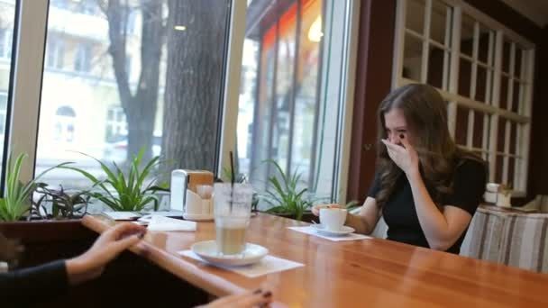 Two young friends woman sitting in cafe, joking and laughing. Two beautiful girls in black dress and red lipstick, drinking coffee in a cafe.