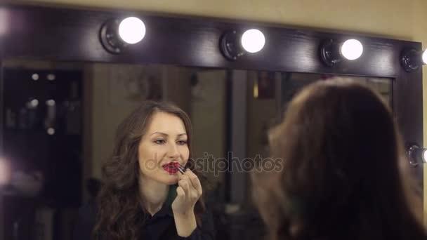 Szexi lány festi a száját a vörös rúzs a tükör. Szépség szalon. Szépség nő