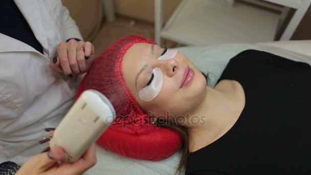 Hlavní kosmetička pracuje s rozprašovač po ošetření, prodlužování řas. Postup prodlužování řas v salonu