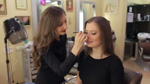 Profesionální vizážistka dělá make-up pro dívky. Kosmetický salon. Krásná žena tvář. Perfektní make-up