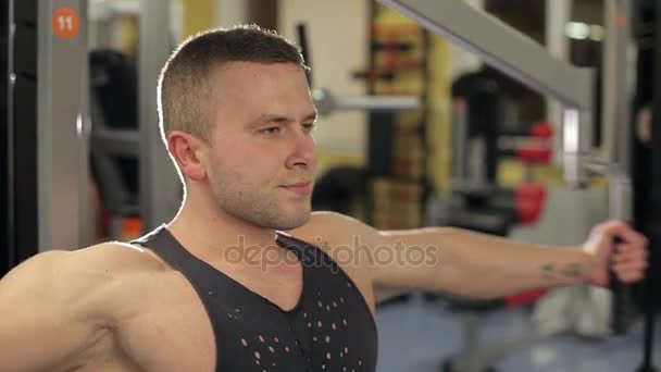 Bodybuilder guy in gym pumping up hands close-up. Muscular man working out in gym and doing exercises at biceps.