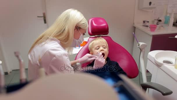 Chlapeček sedí v kanceláři zubařů. Boy hostující specialista na zubní klinice