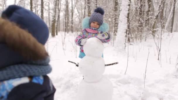 Small children make a snowman in winter Park.