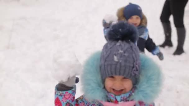 Děti tří až čtyř let hraje na sněhu s rodiči.