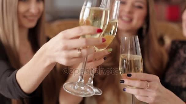 Tři krásné ženy s brýlemi šampaňského slaví na party.
