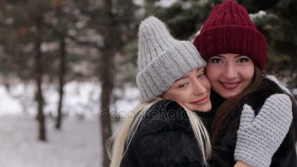 Portrét dvou hezkých dívek v klobouky v zimě.