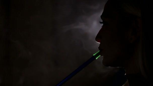 Silueta dívky kouření vodní dýmky na černém pozadí