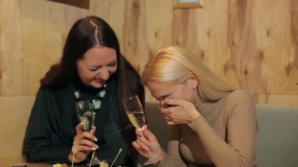 Két fiatal lányok nevettek, és ül egy kávézóban, pezsgővel.