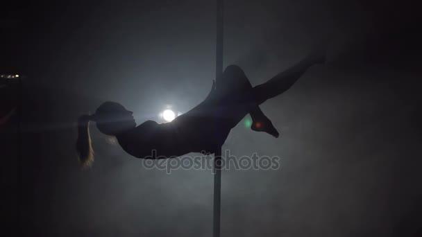 junge Frau beim Training von Pole Dance Fitness, Zeitlupe. Silhouette.