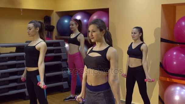 Mladé ženy ve fitness klubu, takže cvičení s činkami, pomalý pohyb