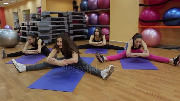 Portrét radost mladých žen dělá protahovací cvičení v tělocvičně