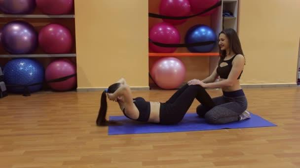 junges schlankes Mädchen schüttelt mit Personal Trainer Bauchmuskeln.