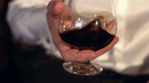 Vířící brandy ve skle, zpomalené. Muž drží sklenku koňaku, detail