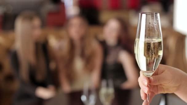 A nőstények kézzel tartani egy pohár pezsgőt, háttérben az emberek egy csoportja