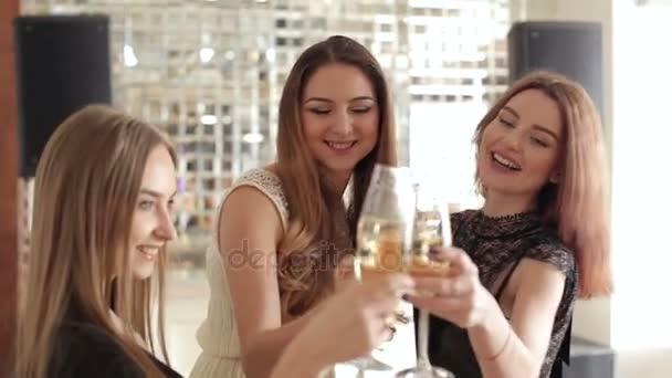 Tři krásné dívky tančí s brýlemi šampaňského v ruce