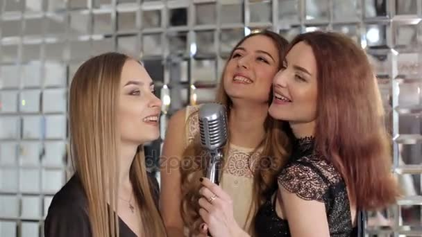 A párt retro mikrofonba énekel, gyönyörű lányok.