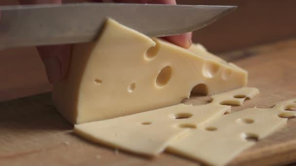 Proces řezání sýr na řezací deska detail, pomalý pohyb.