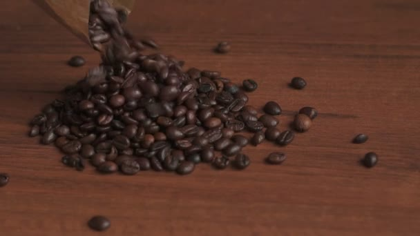 Kávová zrna vylévat na dřevěný stůl, pomalý pohyb