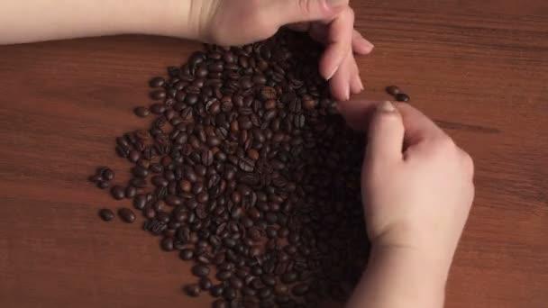 Dívka dává tvar srdce ze zrnkové kávy