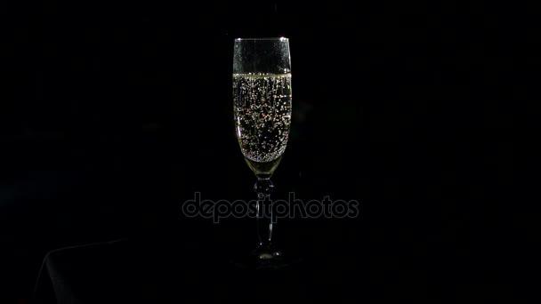 Glas Champagner auf schwarzem Hintergrund, langsam.