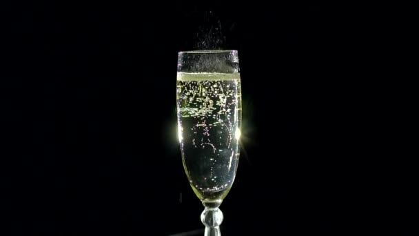 Sklenka šampaňského s bublinami.