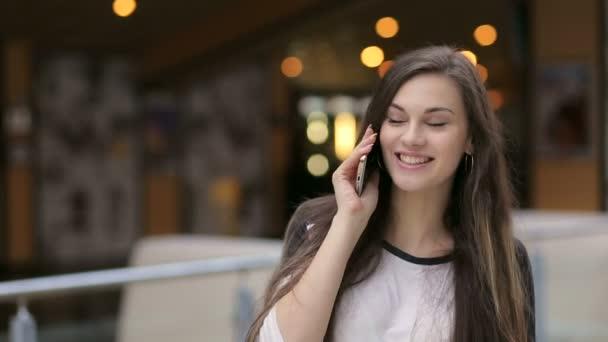 Dívka mluví po telefonu v nákupní centrum.