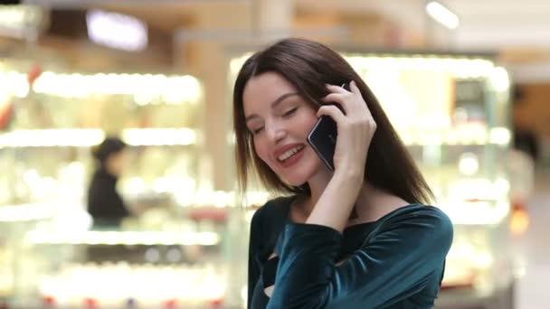 Šťastná žena s nákupní tašky mluví o telefonu
