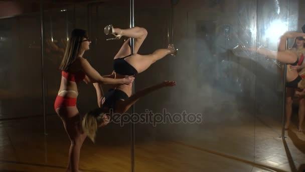 Dvě sexy holky dělají tyčí v tělocvičně